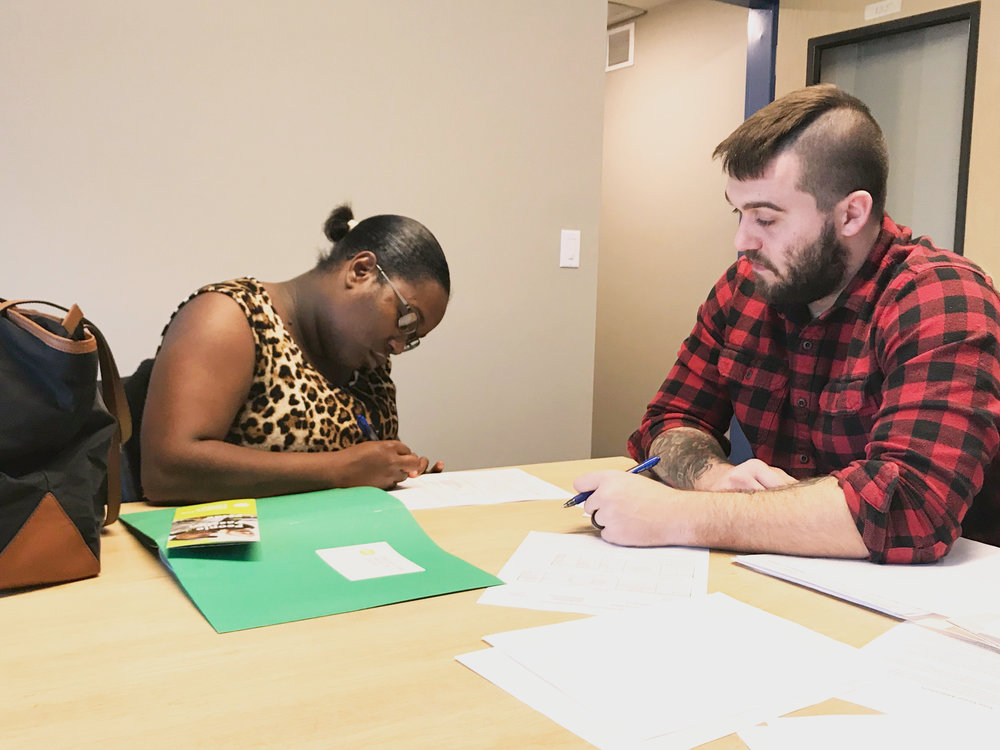 Donia Caldwell signs her lease.  Photo by Mathias Durie.