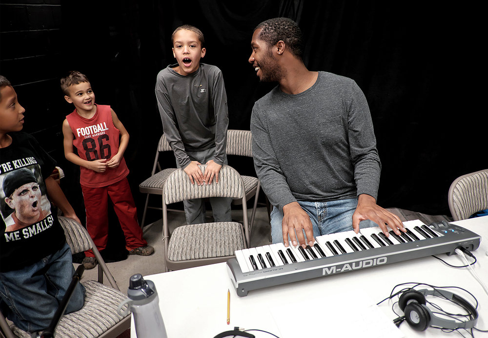 Kyle Rucker leads his students in song as part of an after-school music camp he runs to teach kids about recording and songwriting.
