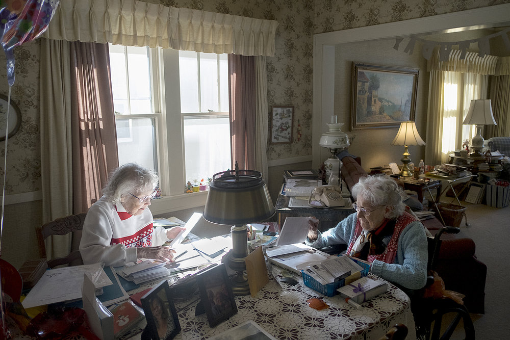 Florence (left) and Jessie, sit at the dining table while Florence goes through bills and recent birthday cards.  Photo by David Pierini