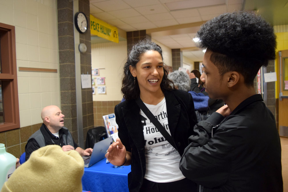 Kristel Porter talks with a young man exploring the North Housing Fair at Lucy Laney Elementary School on March 24. Organized by Porter, who is executive director of the Cleveland Neighborhood Association, the fair connects community members with housing-related resources like construction demonstrations and information about loan programs.  Photo by Kenzie O'Keefe