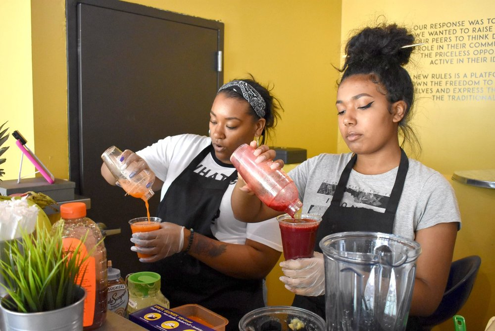 "Sierra Carter (left) and Tierra Armstrong (right) mix up a  ""Jamakin' Me Crazy"" and a ""Respect Your Roots"" at Got the Juice, the new juice and smoothie bar inside New Rules at 2015 Lowry Ave. N. The Jamakin' Me Crazy juice includes carrots, ginger, lemon, pineapple, and orange. The Respect Your Roots juice has beetroot, carrot, orange, apple, and lemon."