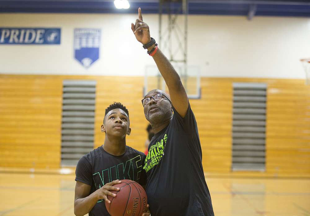 North High Polars basketball coach Larry McKenzie works with incoming freshman Anthony Figures on free throws and follow through.  Photo by David Pierini