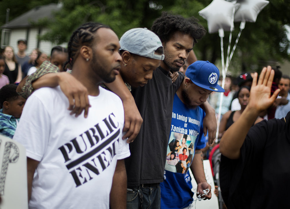 On June 23, Thurman Blevins Jr. was shot and killed by police in the Lind Bohanon neighborhood. A large protest and vigil to honor his memory were held the day after. Here, at the vigil, some of Blevins' cousins, including DaRell Moore, second from right, gathered each other in as they listened to speakers.