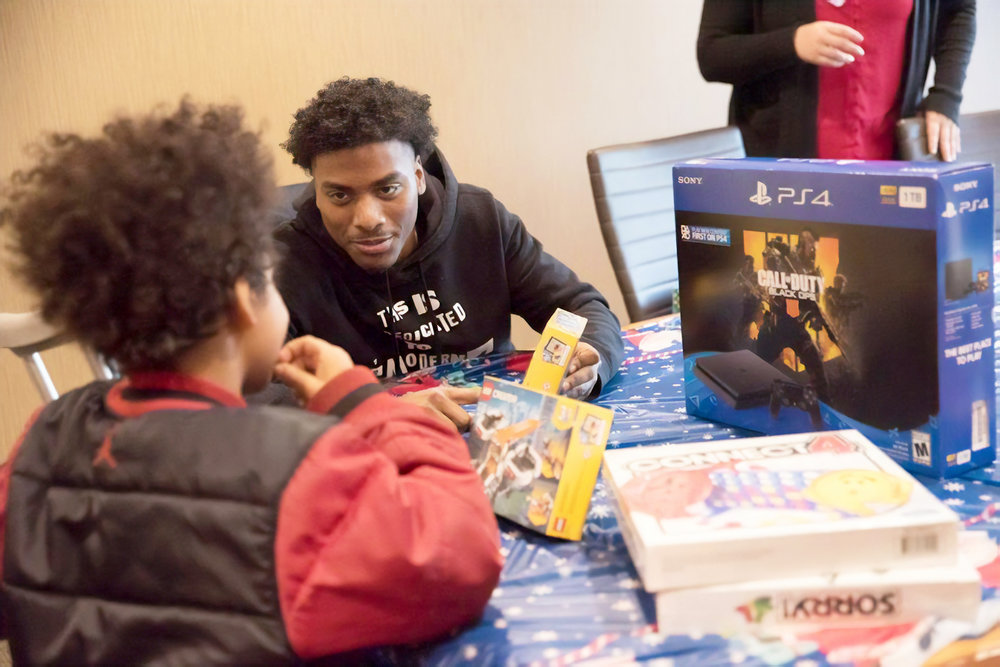 Chris Davis presents a new game console to a nine year old who had recently broken his leg in a car accident during one of the Rashad Vaughn Foundation's gift drives.  Photo courtesy of Chris Davis