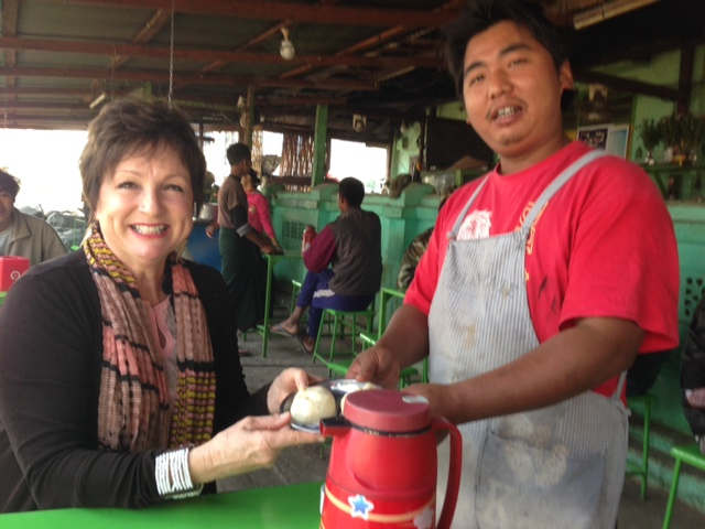 Nancy receives a coconut stuffed steamed bun at a riverside tea shop in Myanmar.