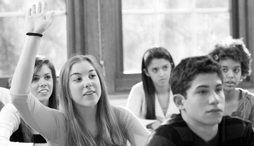 high-school-students-in-classroom-raising-hands-czjyaj6n.jpg