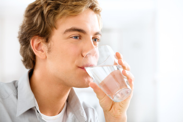 Man drinking a glass of water (Source: paleohacks)