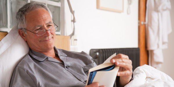 Man reading book in bed (Source:huffpost)