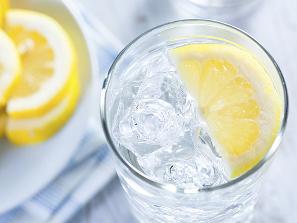 Glass of water with slice of lemon and ice (Source: sharecare)