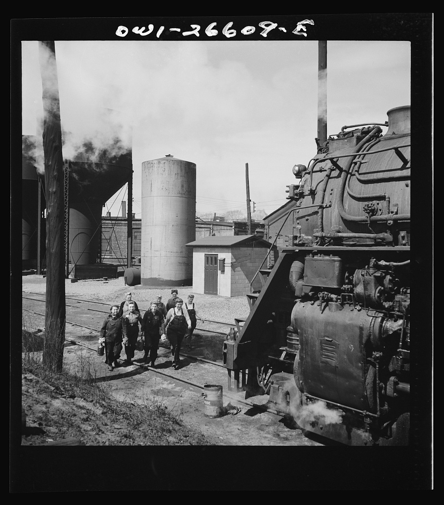 Women wipers of the Chicago and Northwestern Railroad going out to work on an engine at the roundhouse.    Source