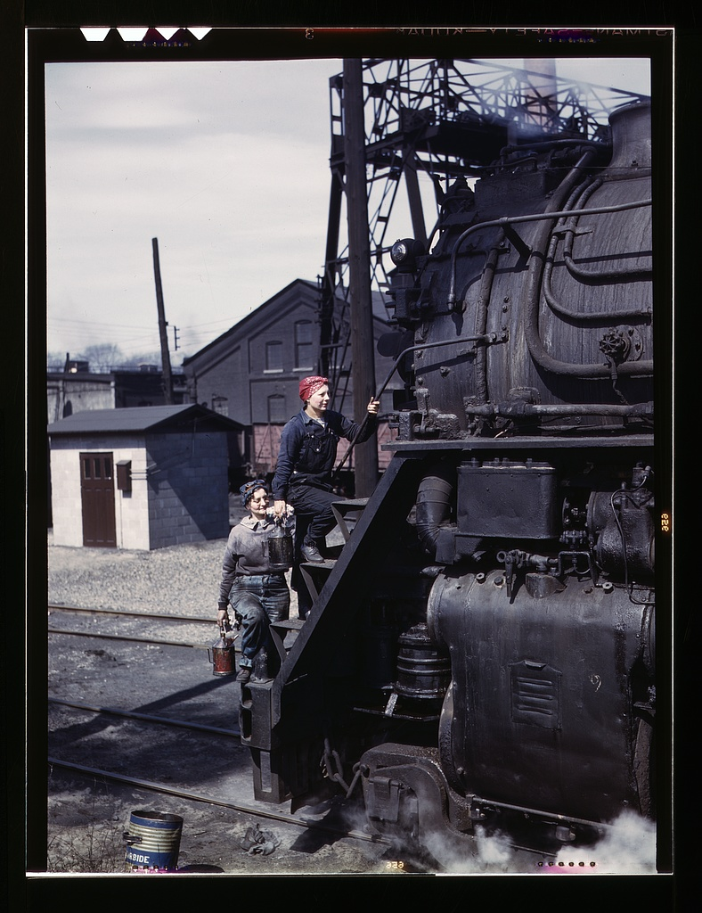 "Marcella Hart and Viola Sievers, women wipers of the Chicago and North Western Railroad cleaning one of the giant ""H"" class locomotives.    Source"