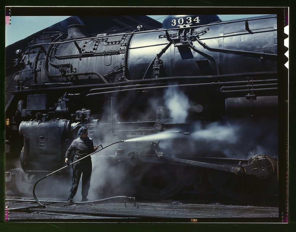 "Viola Sievers, one of the wipers at the roundhouse giving a giant ""H"" class locomotive a bath of live steam.   Source"