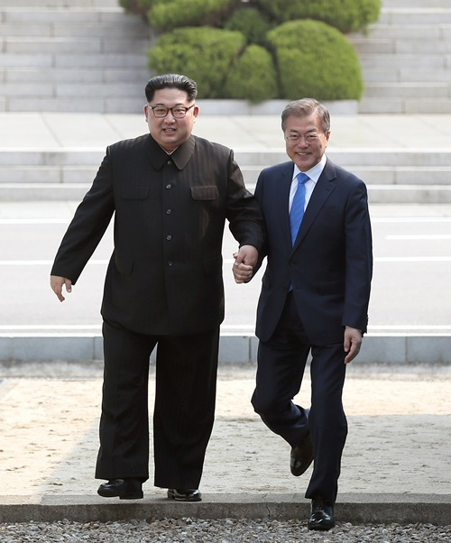 President Moon (right) on April 27 crosses the Military Demarcation Line (MDL) separating the two Koreas with North Korean leader Kim Jong Un, at the truce village of Panmunjeom before their first summit. (2018 Inter-Korean Summit Press Corps)