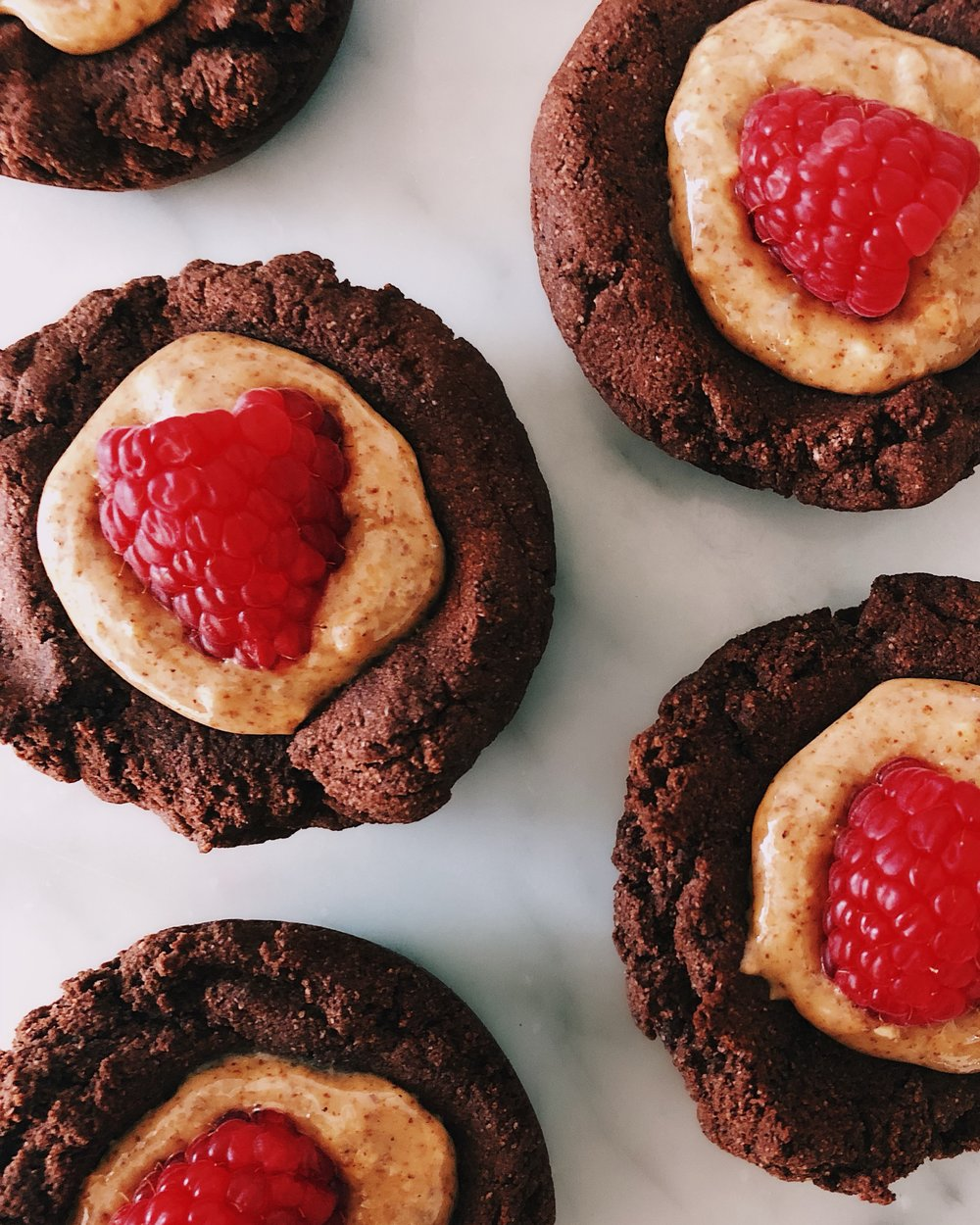 PALEO CHOCOLATE ALMOND BUTTER BITES - INGREDIENTSTHE BASE:1/2 cup cocoa powder1 1/4 cups coconut flour1 cup coconut oil, lightly melted3/4 cup maple syrup1/2 tsp salt1/8 tsp cinnamon (optional)FILLING:1/2 cup almond buttertoppings you desire, such as fresh raspberries!