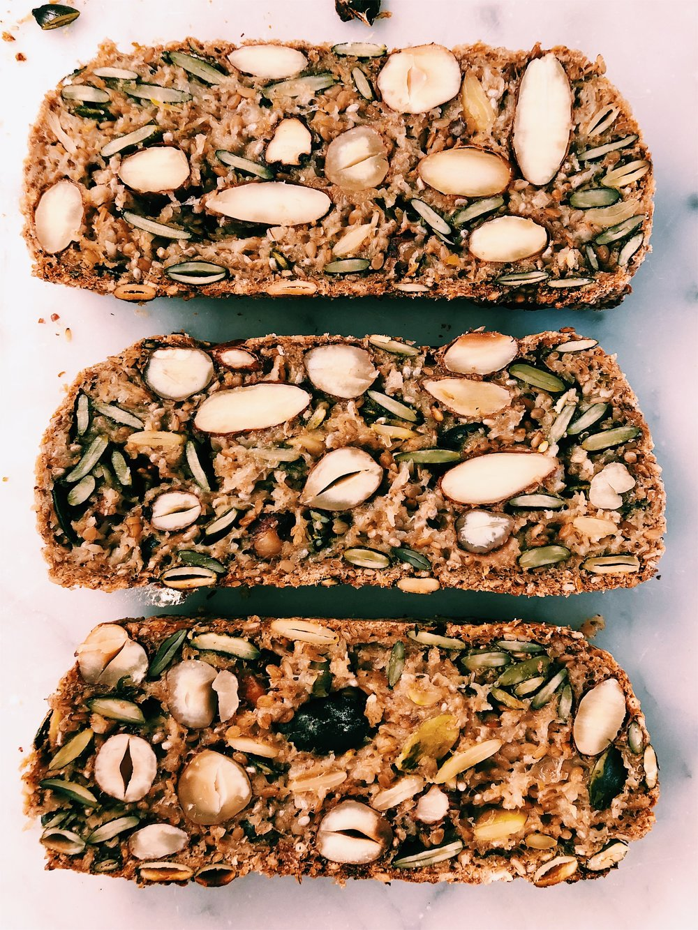 SEED + NUT BREAD - INGREDIENTS1 1/2 cups gluten free rolled oats1 cup pumpkin seeds (or sunflower seeds)1/3 cup almonds1/2 cup hazelnuts1/3 cup sesame seeds1 tsp salt2 1/2 tsp chia seeds3 tb psyllium husks1/4 cup ground flaxseed meal2 tb maple syrup3 tb melted coconut oil (or ghee)1.5 cups warm water