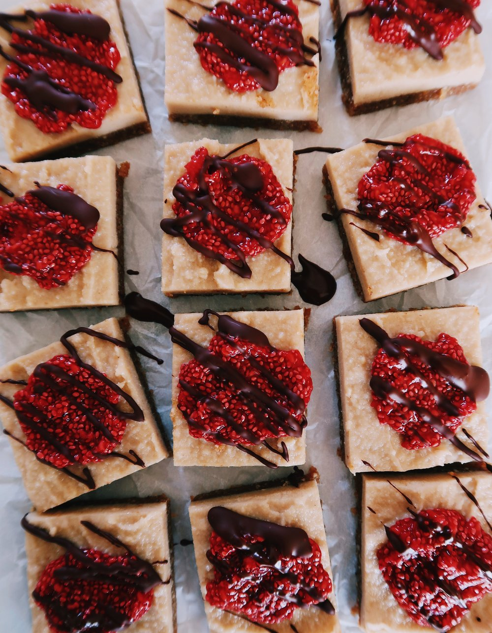 PALEO RASPBERRY CHEESECAKE BARS - INGREDIENTSBASE:1 1/2 cups unsalted walnuts1/2 cup unsalted almonds1/2 cup pitted medjool dates (about 6-7)1/4 cup unsweetened shredded coconutFILLING:3 cups cashews, preferably overnight, or at least 3 hours1/2 cup maple syrup (or honey)Juice of one lemon1/4 melted coconut oil1 tsp vanilla extractTOPPING:1 container organic raspberries1 tb maple syrup4-6 tablespoons chia seeds1 Hu Kitchen chocolate bar of choice (I used the Cashew Butter + Raspberry Jelly Bar)