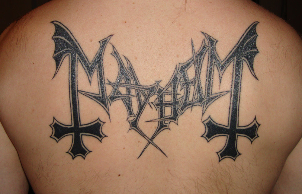 'Mayhem' Logo Tattoo on Jørn 'Necrobutcher' Stubberud of Mayhem.  He used a photo of the tattoo as the cover of his book 'Dødsarkiv'.  First hand chronicle about the first 10 years of his band ' Mayhem ' and the Norwegian Black Metal scene, this time told by an authentic participant/founder as opposed to the many hyped Hollywood versions currently circulating.  Shown in the   press   section of this site.  (Tattoo is healing in this picture)