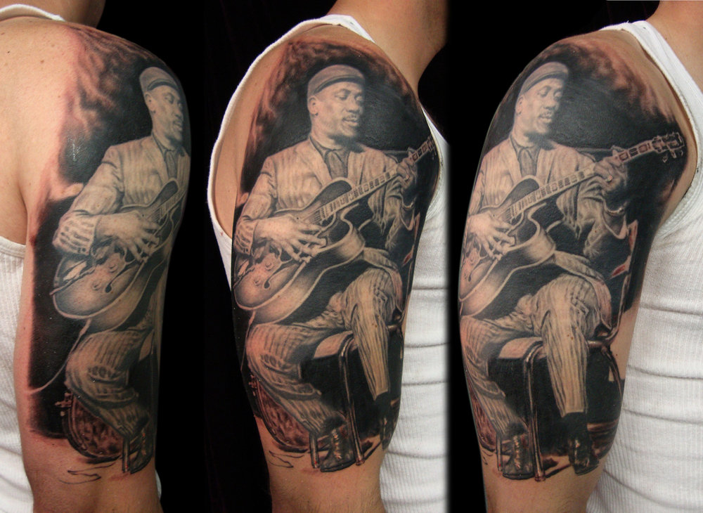 Black and Grey Wes Montgomery Portrait Tattoo, (figure is healed in this photo, background is fresh)