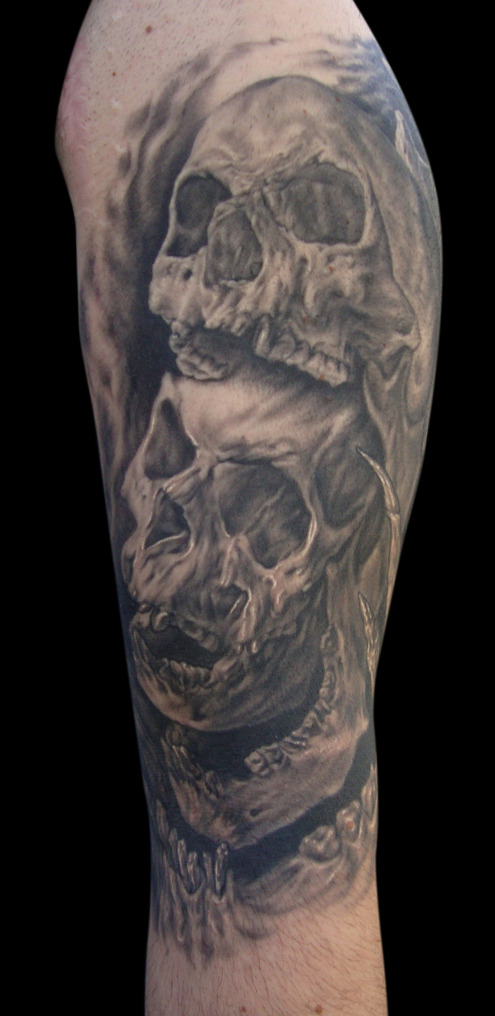 Black and Grey Multi Surreal Skull Overlay Tattoo, (healed) upper arm