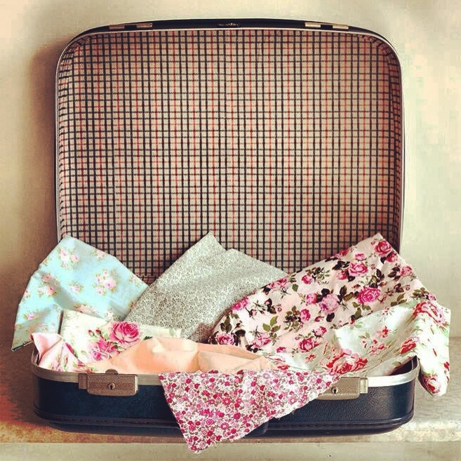 vintage fabrics in vintage suitcase for craft hen party workshop.JPG