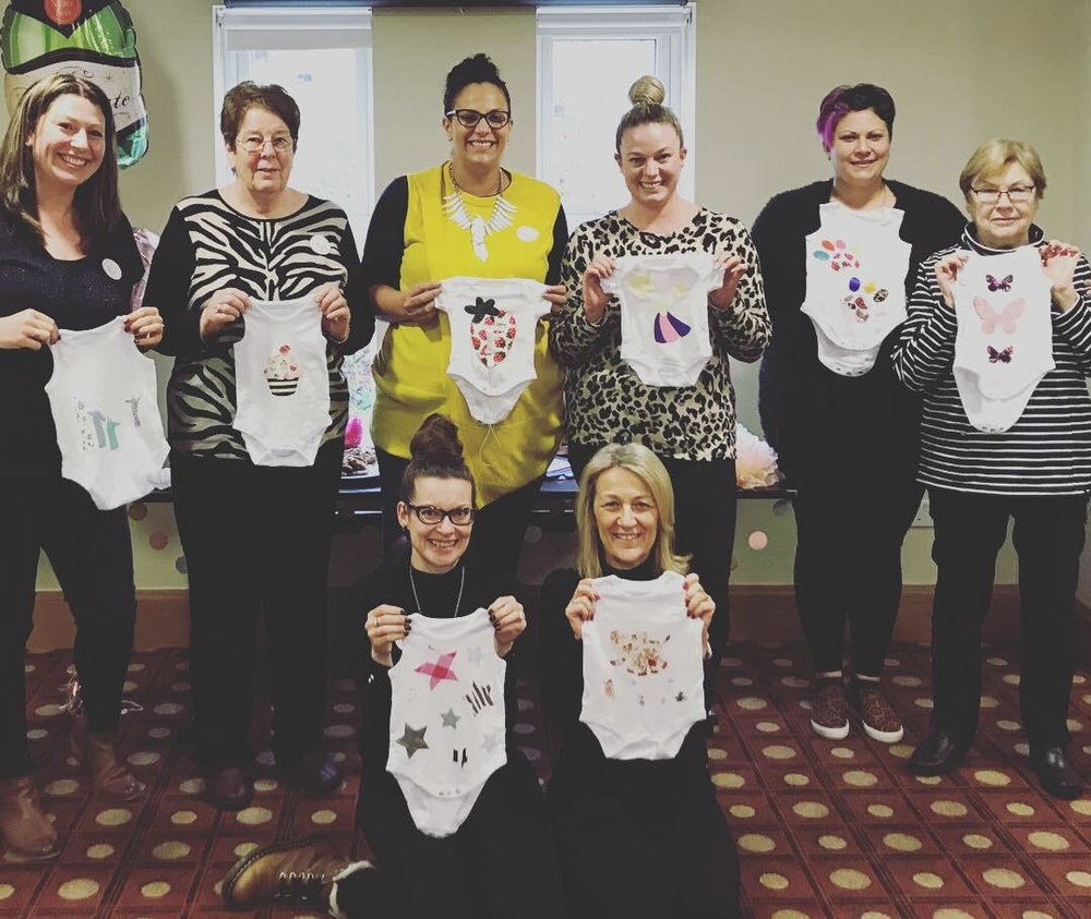 Baby shower group activity customising baby grows