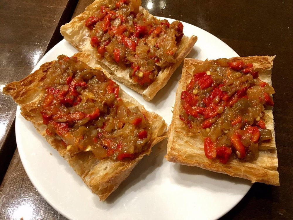 Bread topped with sun-dried tomatoes, sautéed green peppers, and simmered onions