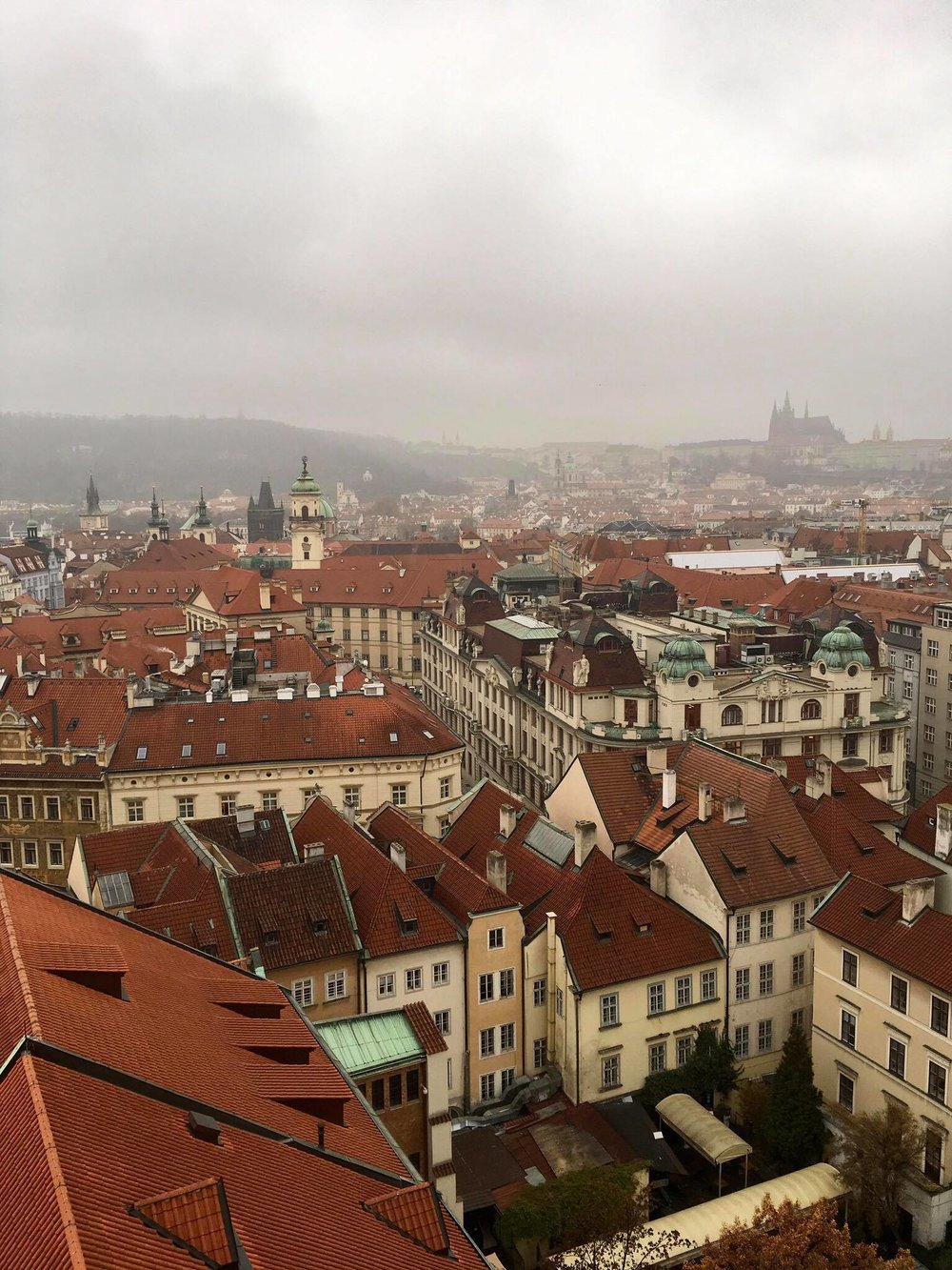 Old town, with an outline of the Prague Castle in the foggy distance.