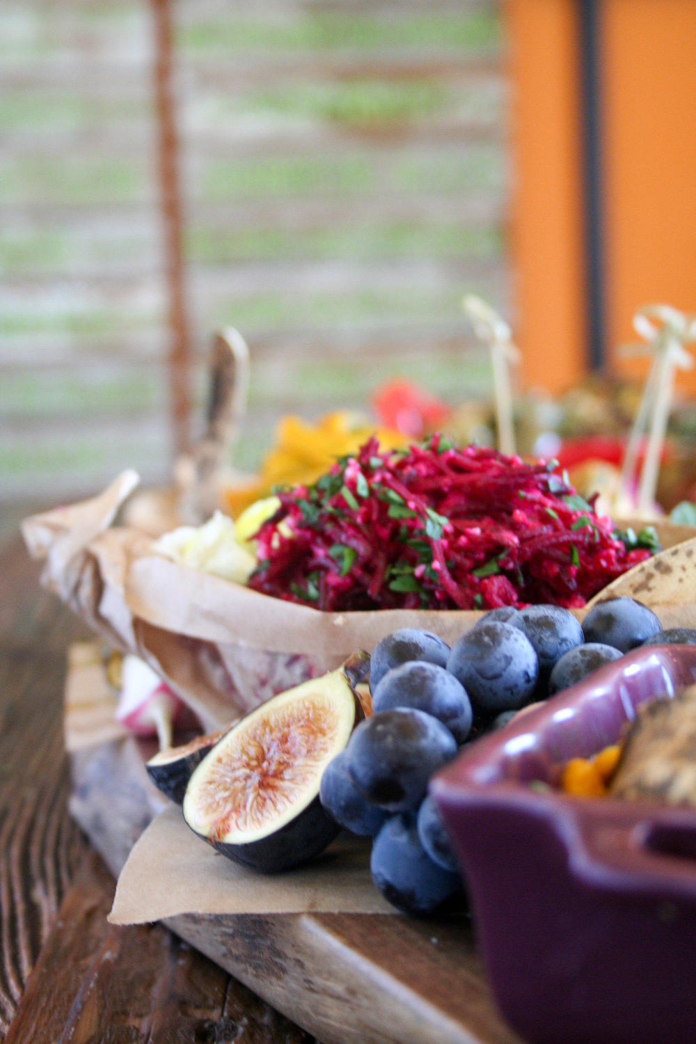 Photo of a Fresh Thymes Marketplace Catering spread focused on a light brown pottery bowl mounding with vibrant magenta beet hummus. Halved fresh Mission Figs in the foreground.
