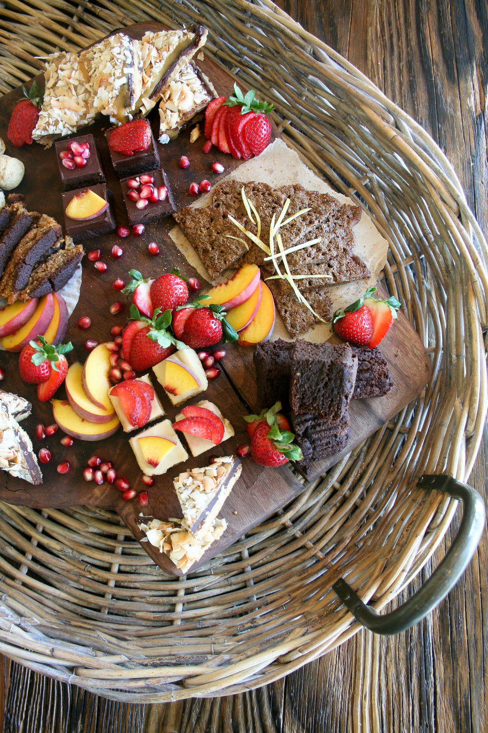 a top-down photo showing a sampling of the catering dessert service from Fresh Thymes Marketplace Catering. On the right is a three-tiered silver tray piled with small bites of brownies, bars, and cookies. On the left are two wooden boards line with large square brownies on one and fruit cheesecakes on the other.