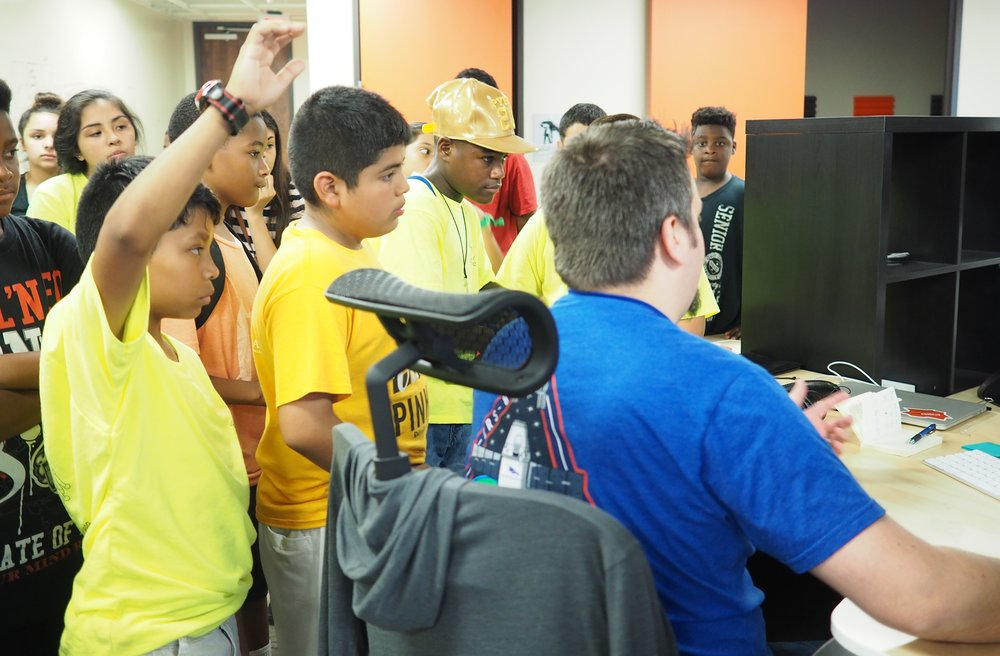 UI Developer Derek Potier demonstrates a current work project to an attentive audience.