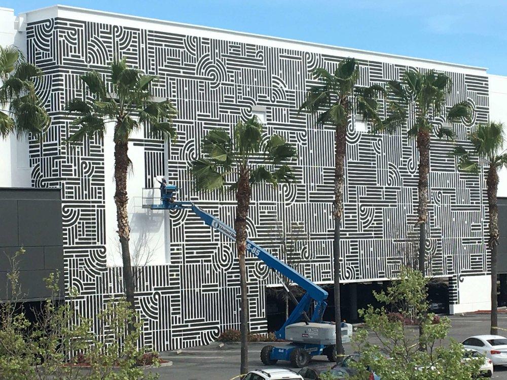 Muralist Aaron de la Cruz completing his project for the AMC Theatre at Eastridge Center in San Jose. Image courtesy  Empire Seven Studios .