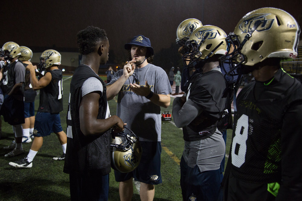 Shelby Bean reviews punt team protocol with freshman Jonathan McCrea, 18, during an evening practice at Gallaudet University on September 30, 2016.
