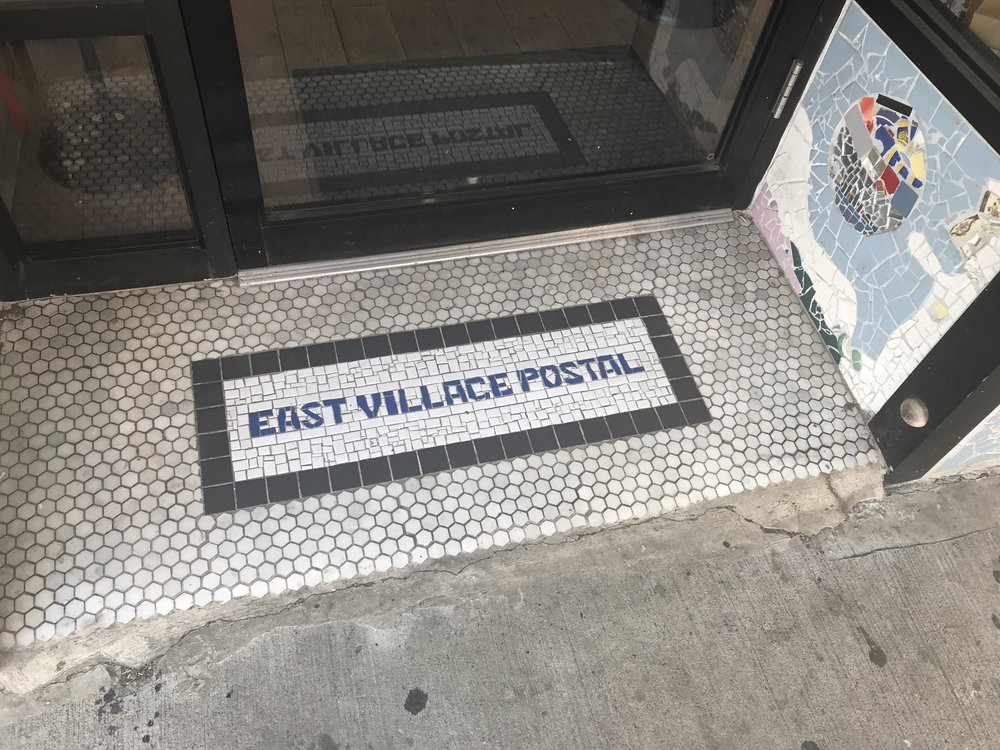 Photo of the East Village Post Office Floor Print, taken sometime in July 2018. Taken because I thought it showed how government services like the post office are fundamental yet often unappreciated -