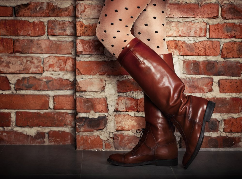 stock-photo-female-legs-in-high-brown-leather-boots-near-the-brick-wall-245081956.jpg