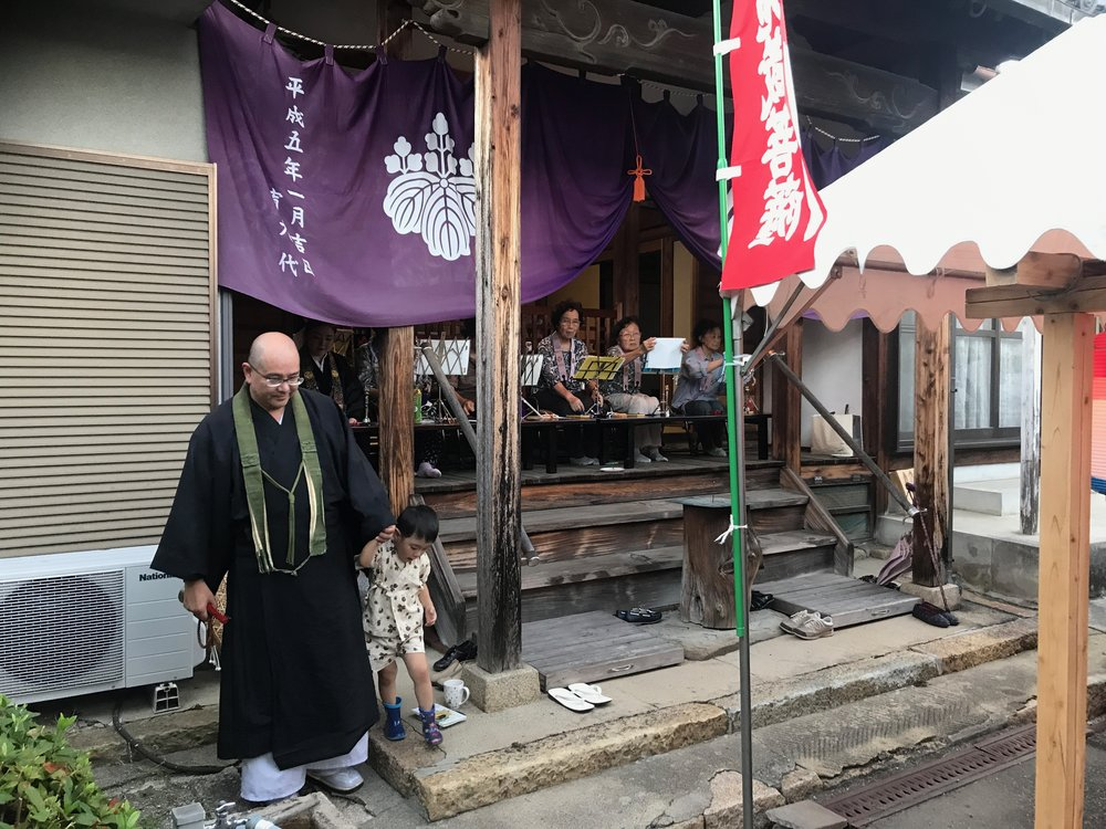 Yoshi, Saho's dad, in his priest's robes, with Yuri, her mum, leading the women's chanting on the temple steps