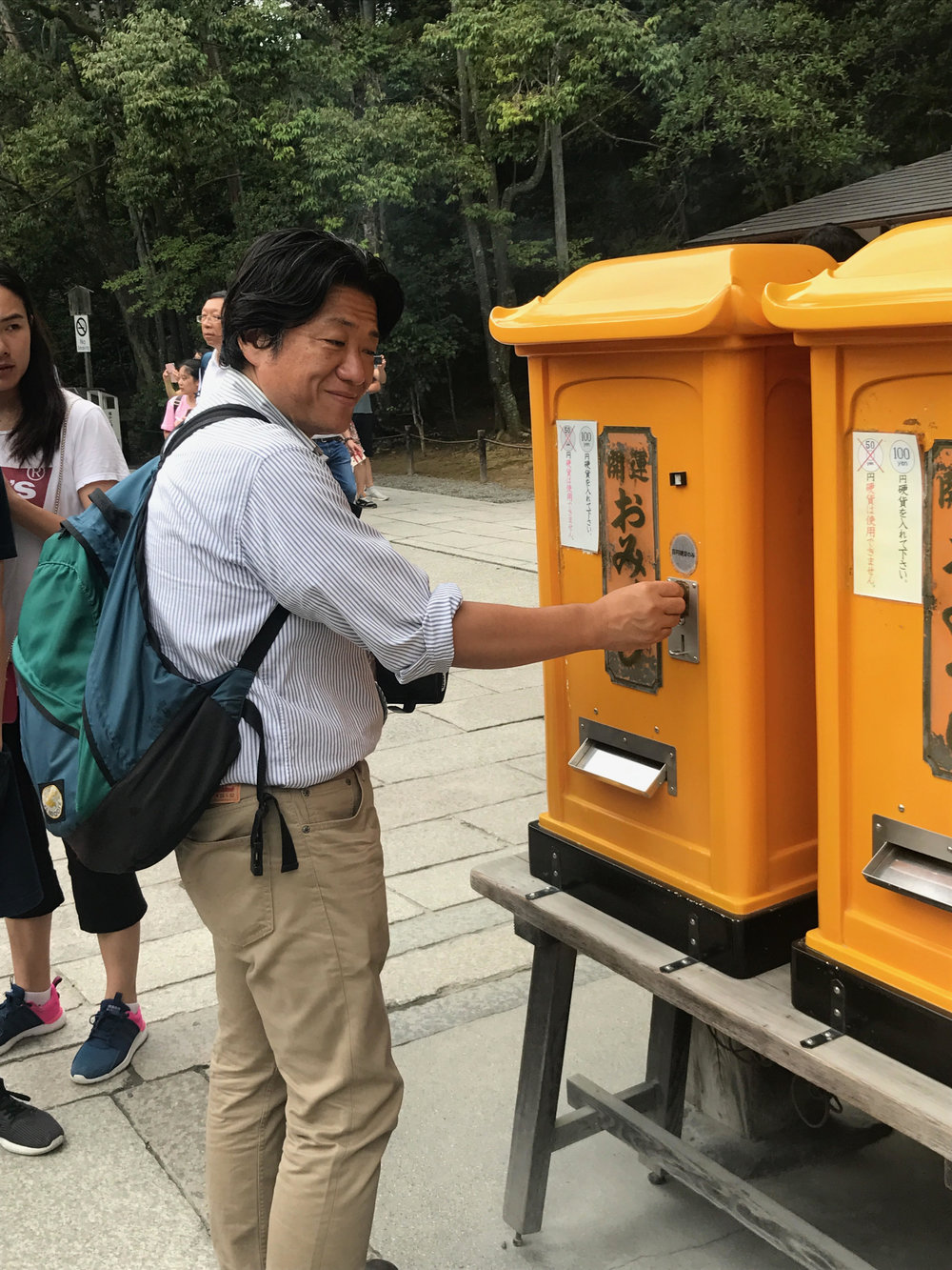 Shiga-san trying his luck with a yellow fortune-telling machine