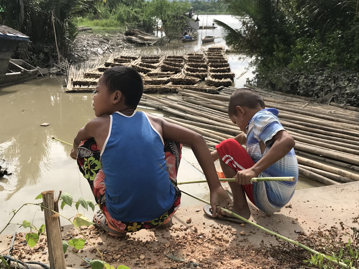 Kids fishing for mudskippers in a creek off the Dawei river. I'm not sure what the bamboo rafts are for - a holding place for bamboo before it's sold, or do they use them for transport?
