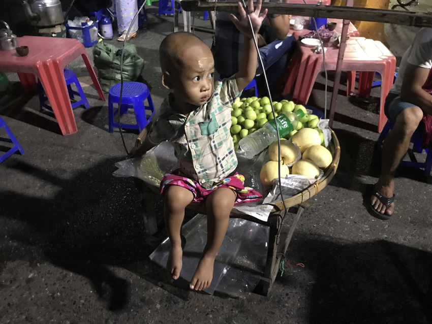 Both this little guy's parents are fruit-sellers, working the streets with their wares in baskets on a bamboo pole. That would be a hard life.