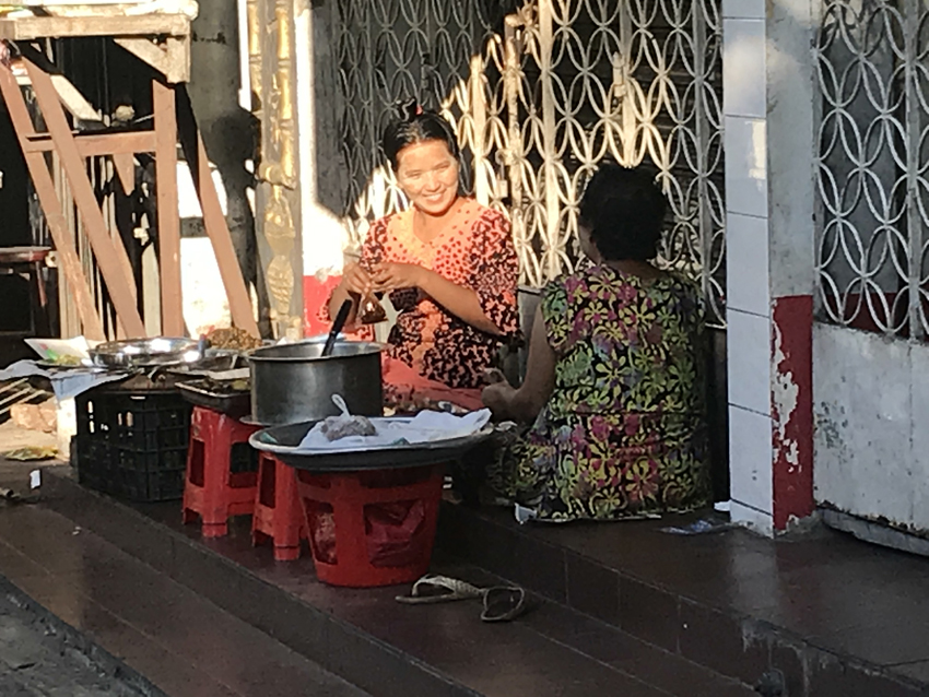 Two women selling breakfast have an early morning chat