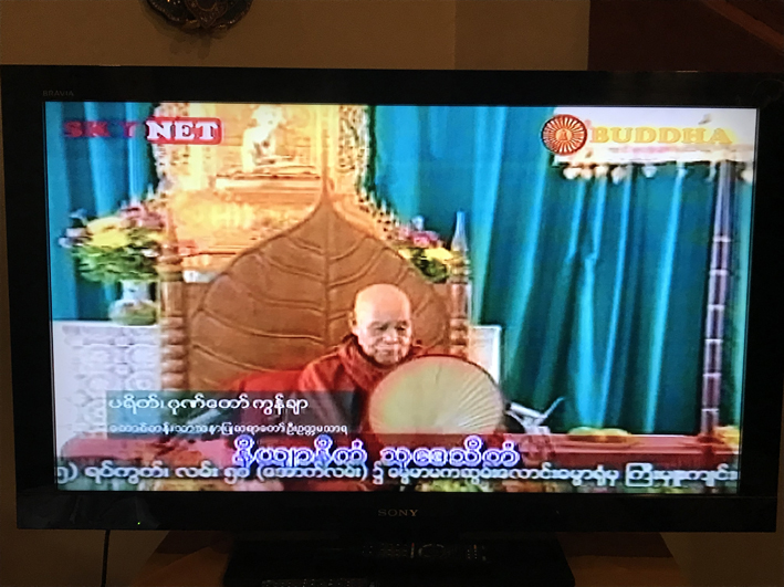 The larger words underneath are what the monk is saying, in an old religious language that even most Burmese speakers can't read. Below that in smaller print is (if I understood correctly) religious news.
