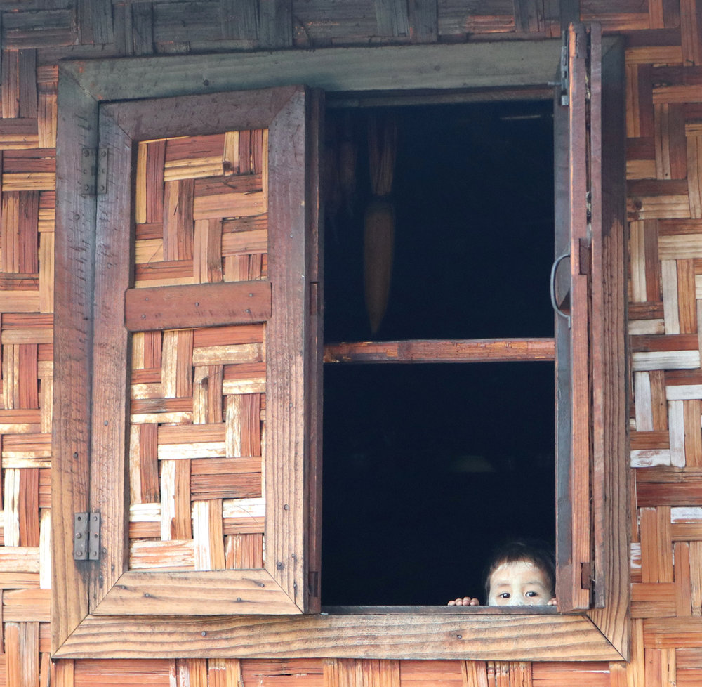 These lovely woven panels are typical of houses in this area. The photogenic kid is extra. Below, a small boy eating breakfast in a similar woven house. And below that, the same house again, actually a small shop - zoomed out. I just think they are so pretty.