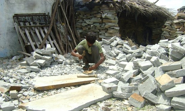 Child labourer works at sandstone in a South India quarry.