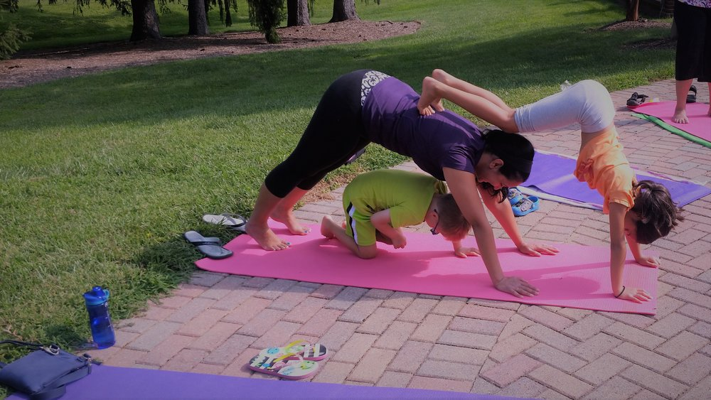 "double down-dog (with a little yoga ""puppy"" underneath!) at one of our Shining Kids Yoga Outdoor Family classes!"
