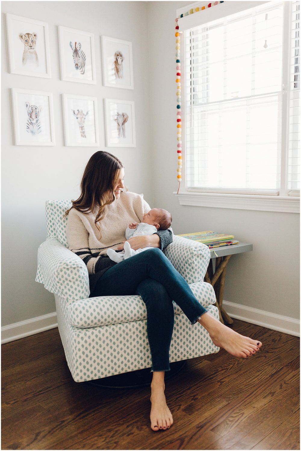 Mother Sitting In Rocking Chair With Newborn Son In Nursery