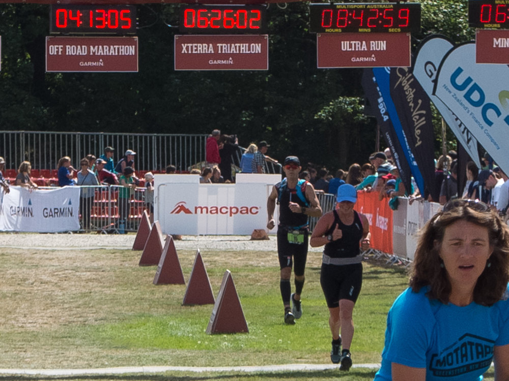 Crossing the finish line with a bonus photobomb to my left.