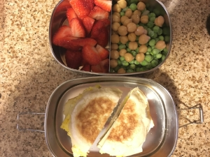 Scrambled egg and a slice of cheese on an english muffin with strawberries, peas and garbonzo beans.