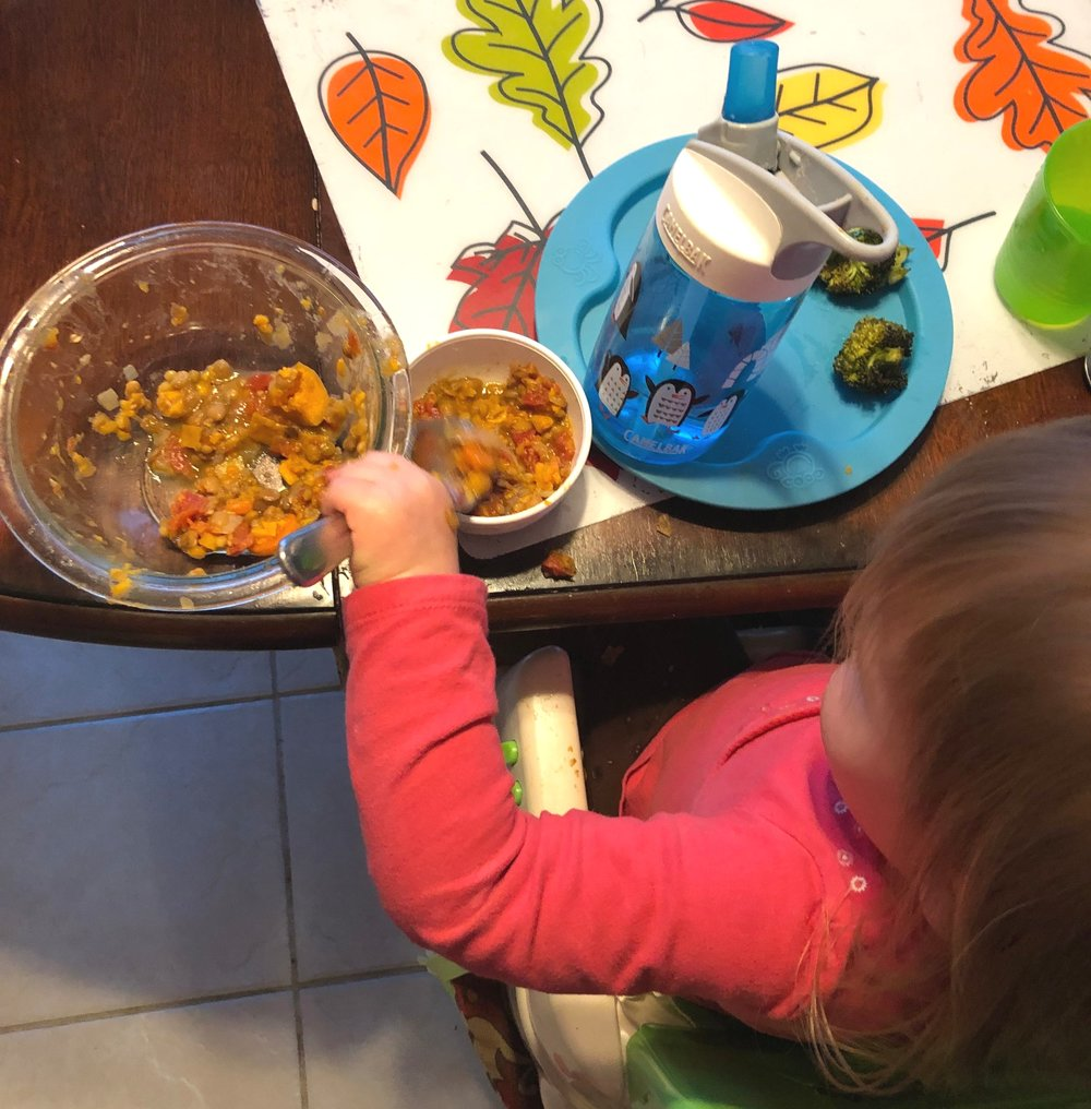 "Alexandra, 20 months, spooning chili from the large ""family style"" bowl into her dinner bowl."