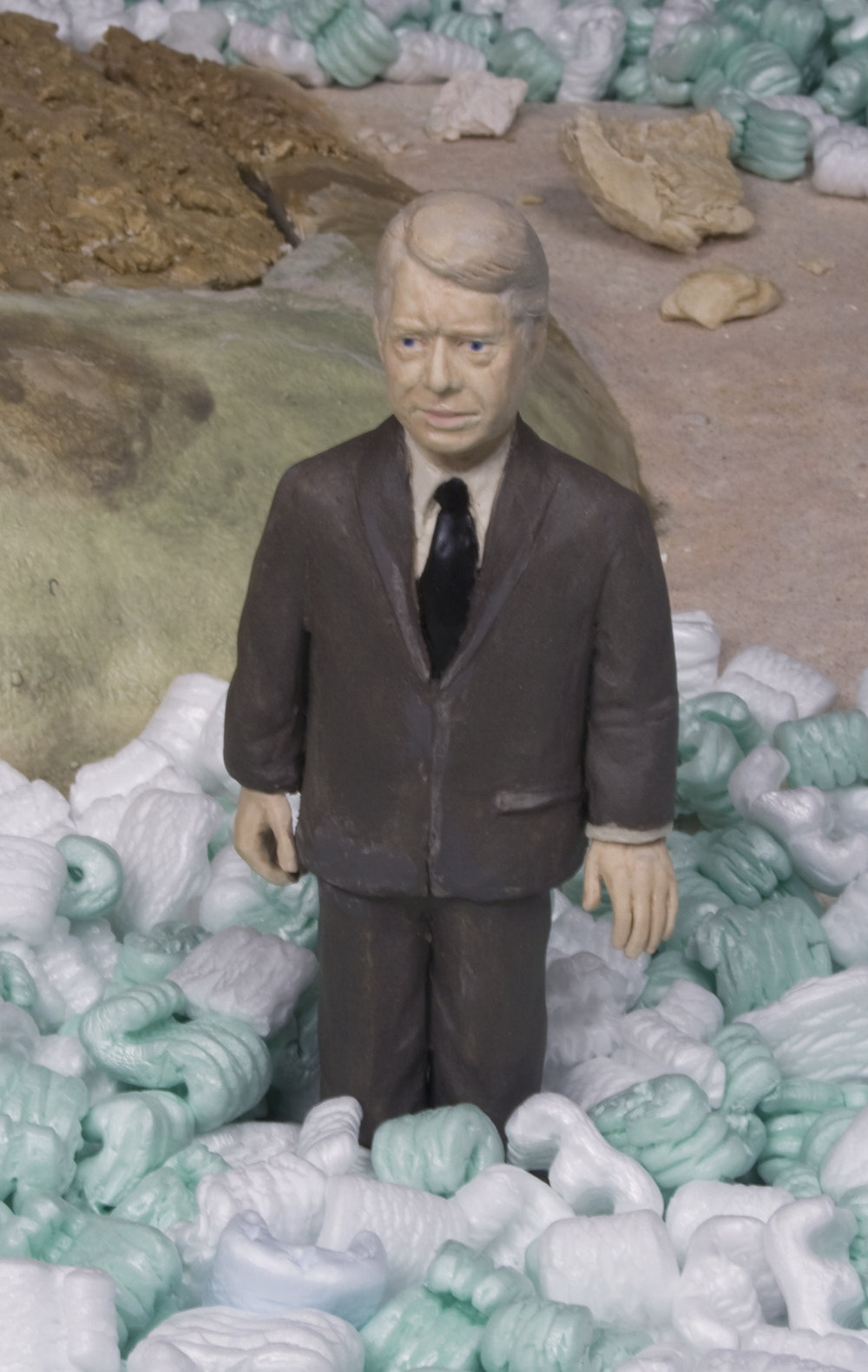 Landscape with the Fall of Torrijos       Glazed cone 5 porcelain, cardboard, styrene peanuts, mixed media Detail of Jimmy Carter 2008