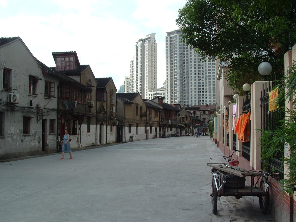 An old Hutong-style roadway in Shanghai, contrasting with high-rise apartments towering behind.