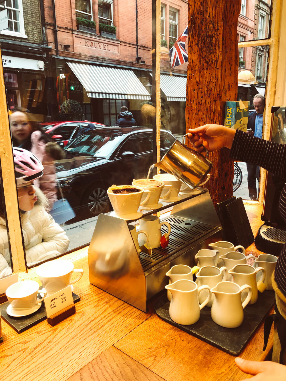Monmouth Coffee London - pour over coffee being made in the window with pitchers of samples below